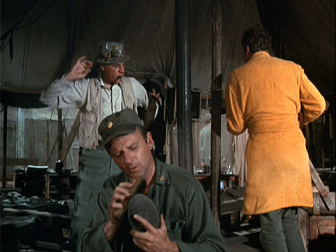 Colonel Blake and Trapper singing and dancing behind Frank, who is shining his shoe