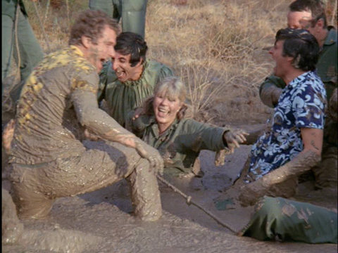 Still from the M*A*S*H episode Bulletin Board showing characters in the mud.