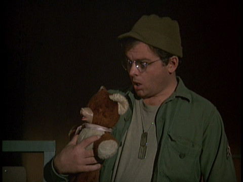 Screenshot featuring Gary Burghoff as Radar, holding his teddy bear and looking surprised