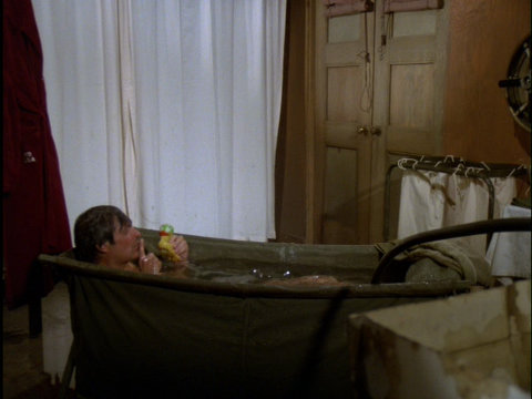 Still from the M*A*S*H episode None Like It Hot showing Hawkeye in a bath tub.