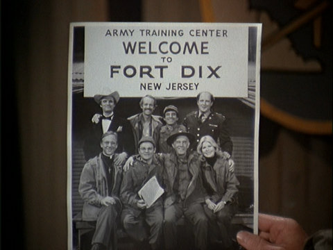 Still from the M*A*S*H episode The Party showing the cast in front of a Fort Dix sign.