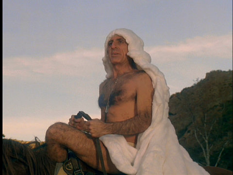 Image of Klinger, atop Sophie the horse, wearing nothing but a white sheet