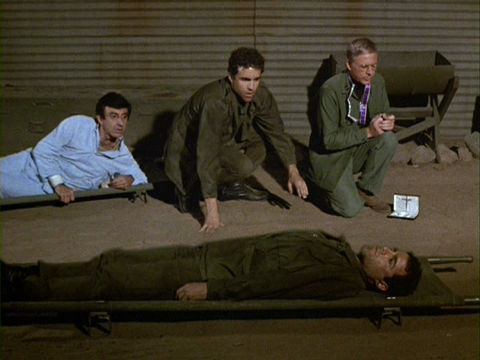 Private Weston has stepped out of his dead body and is crouched between Klinger and Father Mulcahy