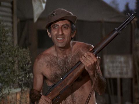 Klinger naked holding a rifle