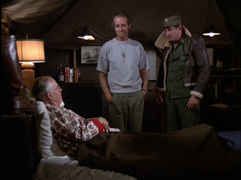 Charles wearing a jacket that is too small for him in Colonel Potter's tent
