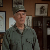 Colonel Potter, standing behind his desk in his office