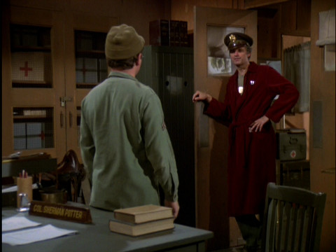 Hawkeye wearing an army cap and his bathrobe standing in Colonel Potter's doorway