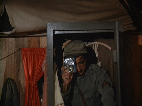 Klinger in a closet taking a photograph