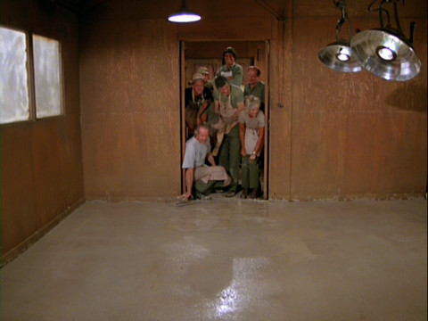 Members of the 4077th in the doorway of the O.R. looking at the new floor