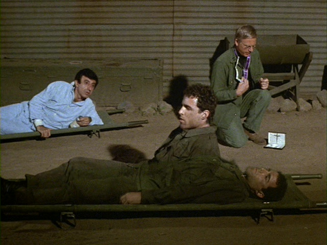 Still from the M*A*S*H episode Follies of the Living-Concerns of the Dead showing Klinger, Private Weston, and Father Mulcahy.