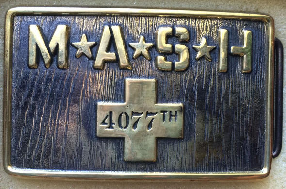 Picture of a brass belt buckle with the words M*A*S*H 4077th on it.