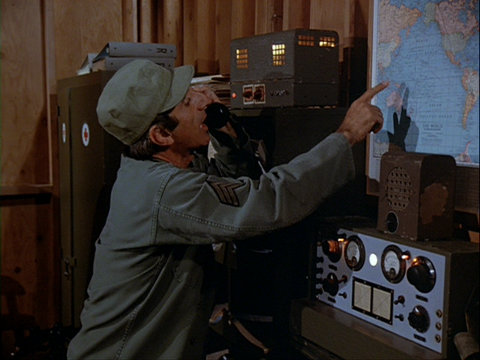 Still from the MASH episode Goodbye Farewell and Amen showing Klinger next to the radio/PA system.