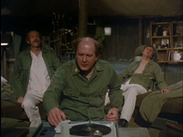 Still from the M*A*S*H episode Ain't Love Grand showing Charles listening to music