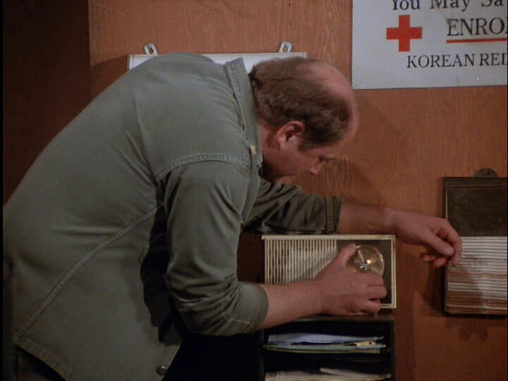 Still from the M*A*S*H episode A War for All Seasons showing Charles tuning a radio.