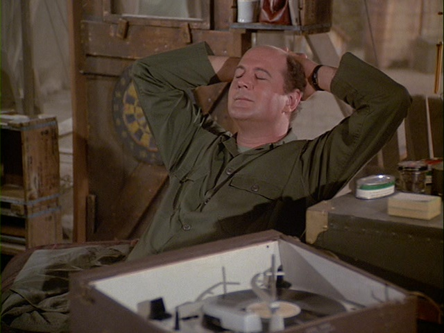 Still from the M*A*S*H episode Picture This showing Charles listening to music.