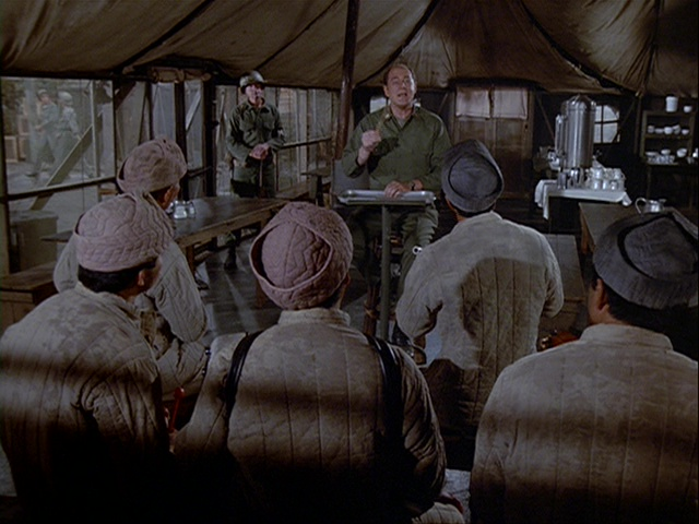 Still from the M*A*S*H episode Goodbye Farewell and Amen showing Charles conducting the POWs.